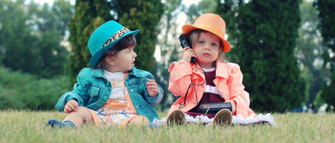 Een kind in het gras belt met een telefoon